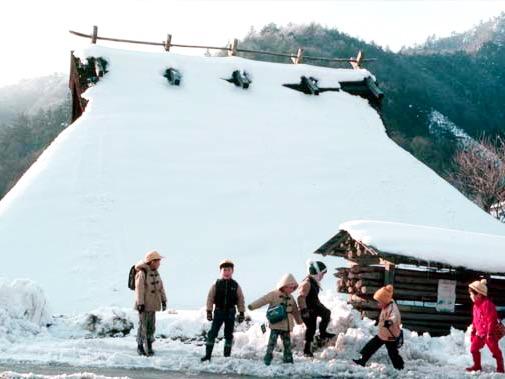 雪のかやぶき屋根と子ども達